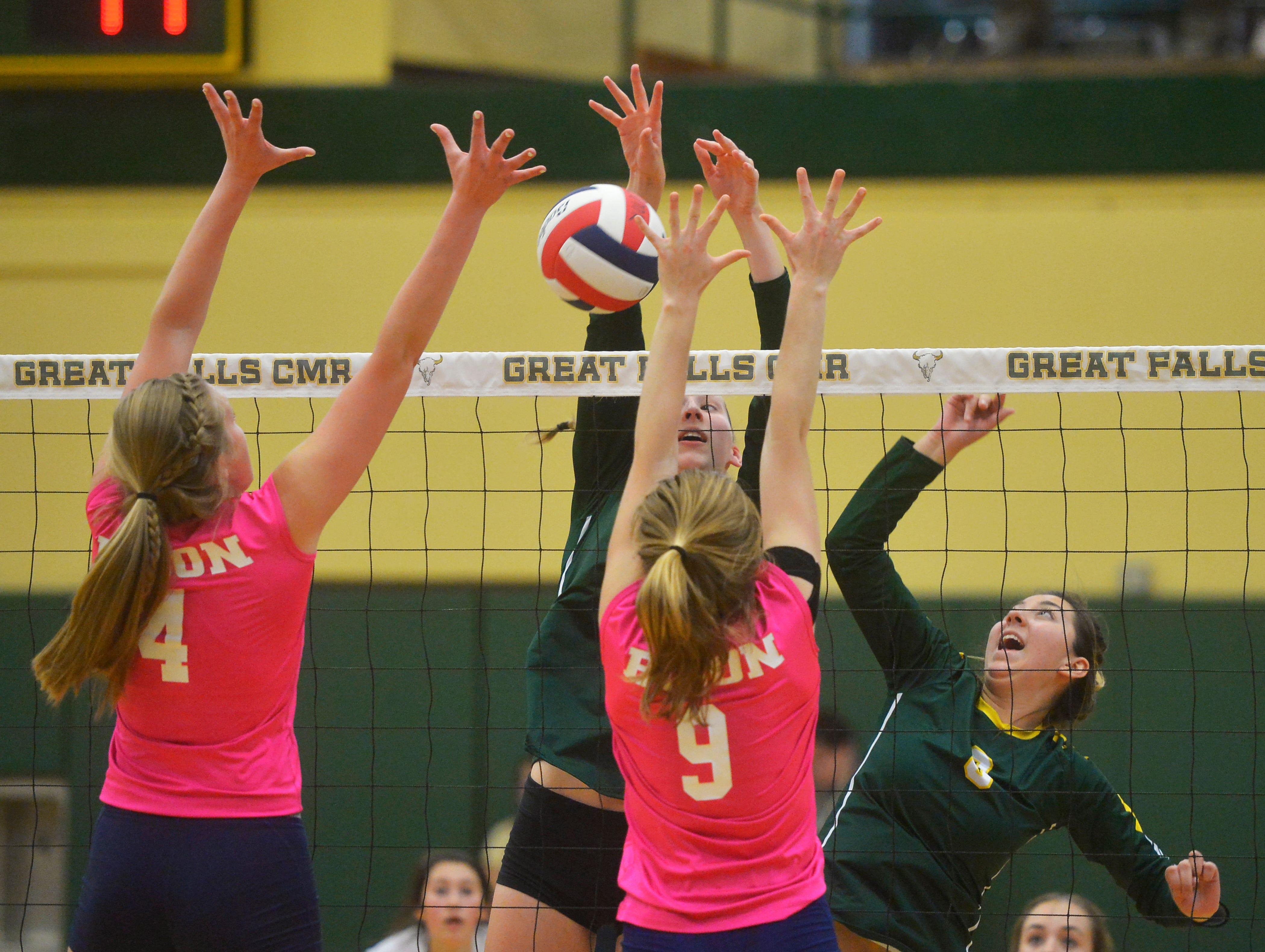 CMR's Allie Olsen and Alexis Gonzales battle at the net with Great Falls High's Abbie Groskreutz, 4, and Malena Bruskotter, 9, during the crosstown volleyball match in the CMR Fieldhouse, Tuesday.