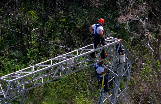 FILE - In this Sunday, Oct. 15, 2017, file photo, Whitefish Energy Holdings workers restore power lines damaged by Hurricane Maria in Barceloneta, Puerto Rico. A year after losing a $300 million no-bid contract to restore Puerto Rico's hurricane-shattered electric grid, Whitefish Energy Holdings has quietly been seeking and winning U.S. government contracts. (AP Photo/Ramon Espinosa, File)
