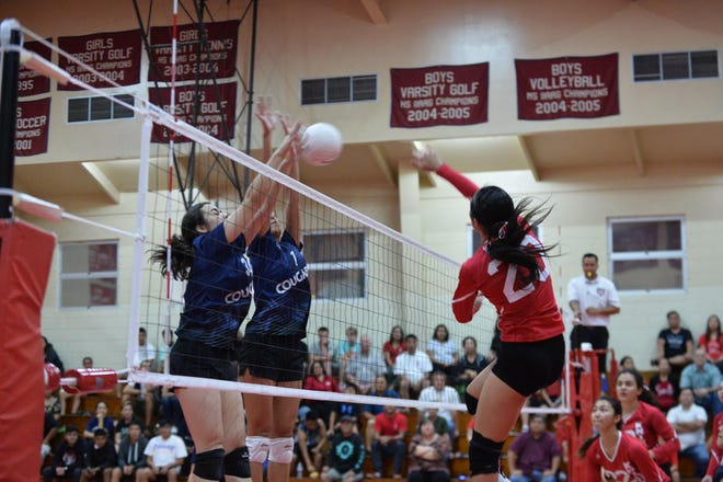 St. John's Hallie Wigsten, No. 20, hits past the Cougar block of Isabella Bargfrede, No. 34 and Laressa Halladay, No. 1 in their semifinal game Oct. 9 at the Dale Jenkins Gym. St. John's won in 5 sets to advance to the championship game.