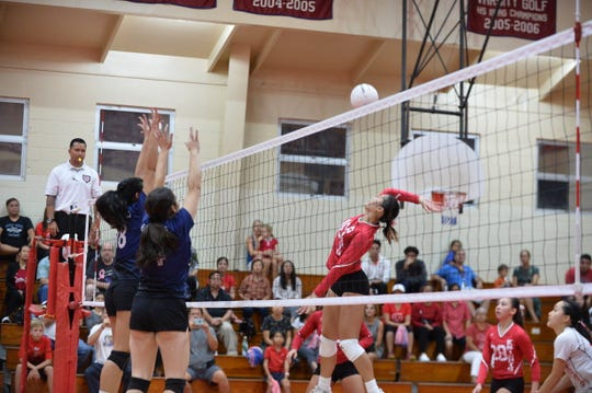 St. John's Knights middle blocker Angeline Del Carmen, right, goes up against the Academy Cougar block of Theisen Taimanglo, left and Isabella Bargfrede, center in the Knights' 5-set win over Academy Oct. 9 at St. John's.
