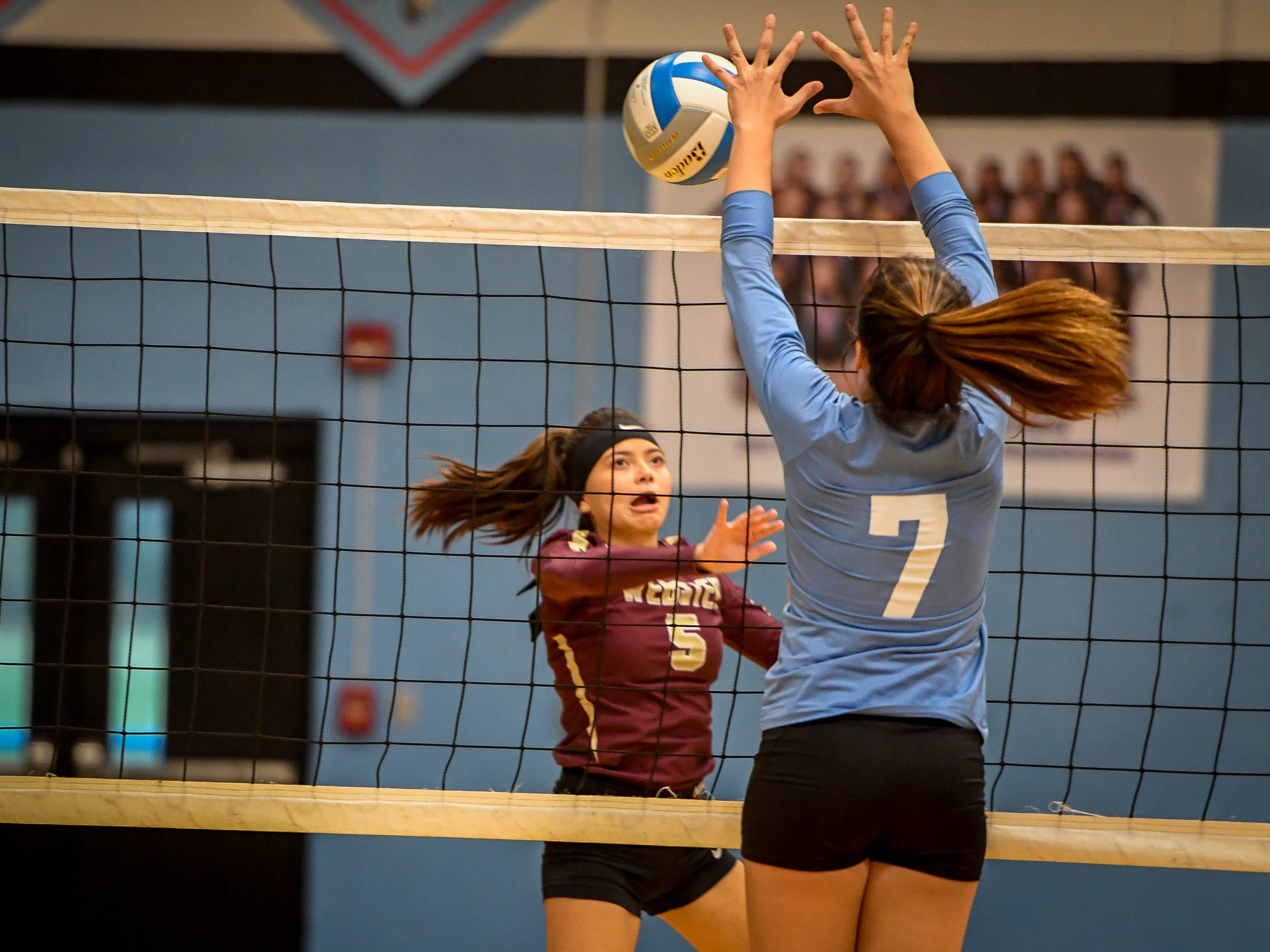 Webster's Adrianna Lopez (5)  and Union's Emily Hibbs (7) battle at the net as the Webster County Lady Trojans play the Union County Bravettes in the District Volleyball Tournament in Morganfield, Tuesday, October 9, 2018.