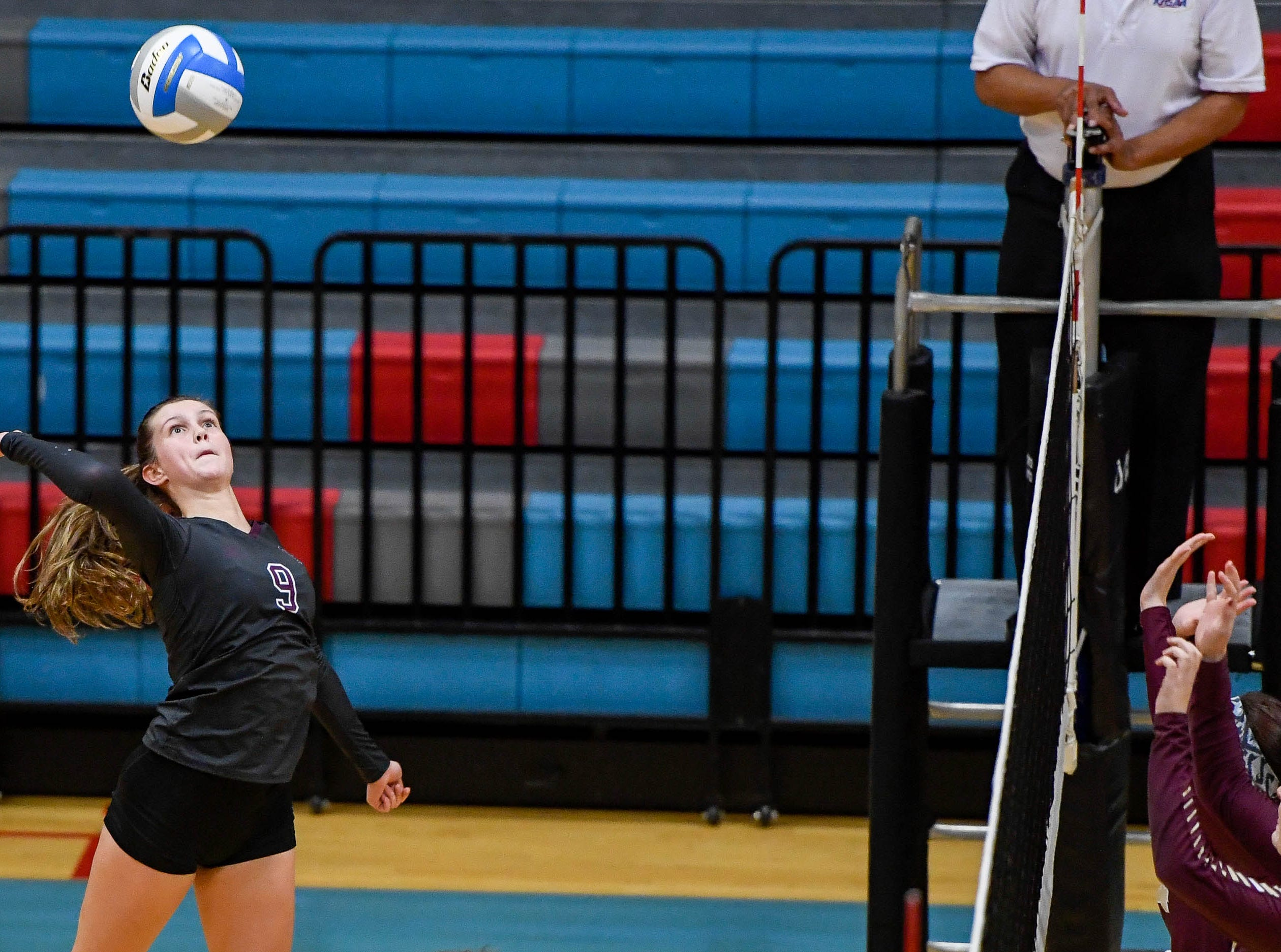 Henderson's Jordan Troutman (9) attacks at the net as the Henderson County Lady Colonels play the Webster County Lady Trojans in the District Volleyball Tournament championship match in Morganfield, Tuesday, October 9, 2018.