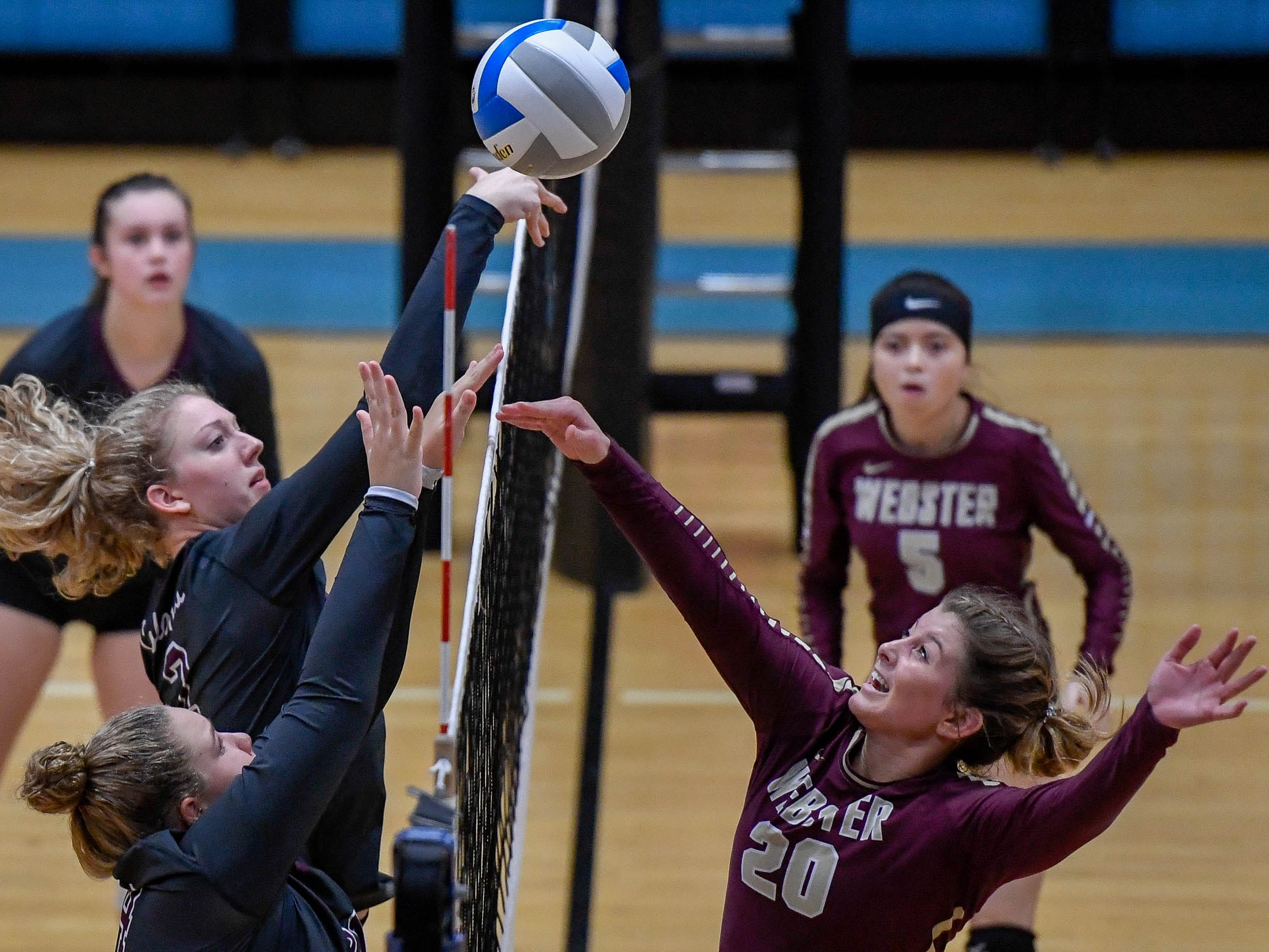 Henderson's Brooke Springer (2) and Maddison Williams (24 battle Webster's Lana Eastwood (20) as the Henderson County Lady Colonels play the Webster County Lady Trojans in the District Volleyball Tournament championship match in Morganfield, Tuesday, October 9, 2018.