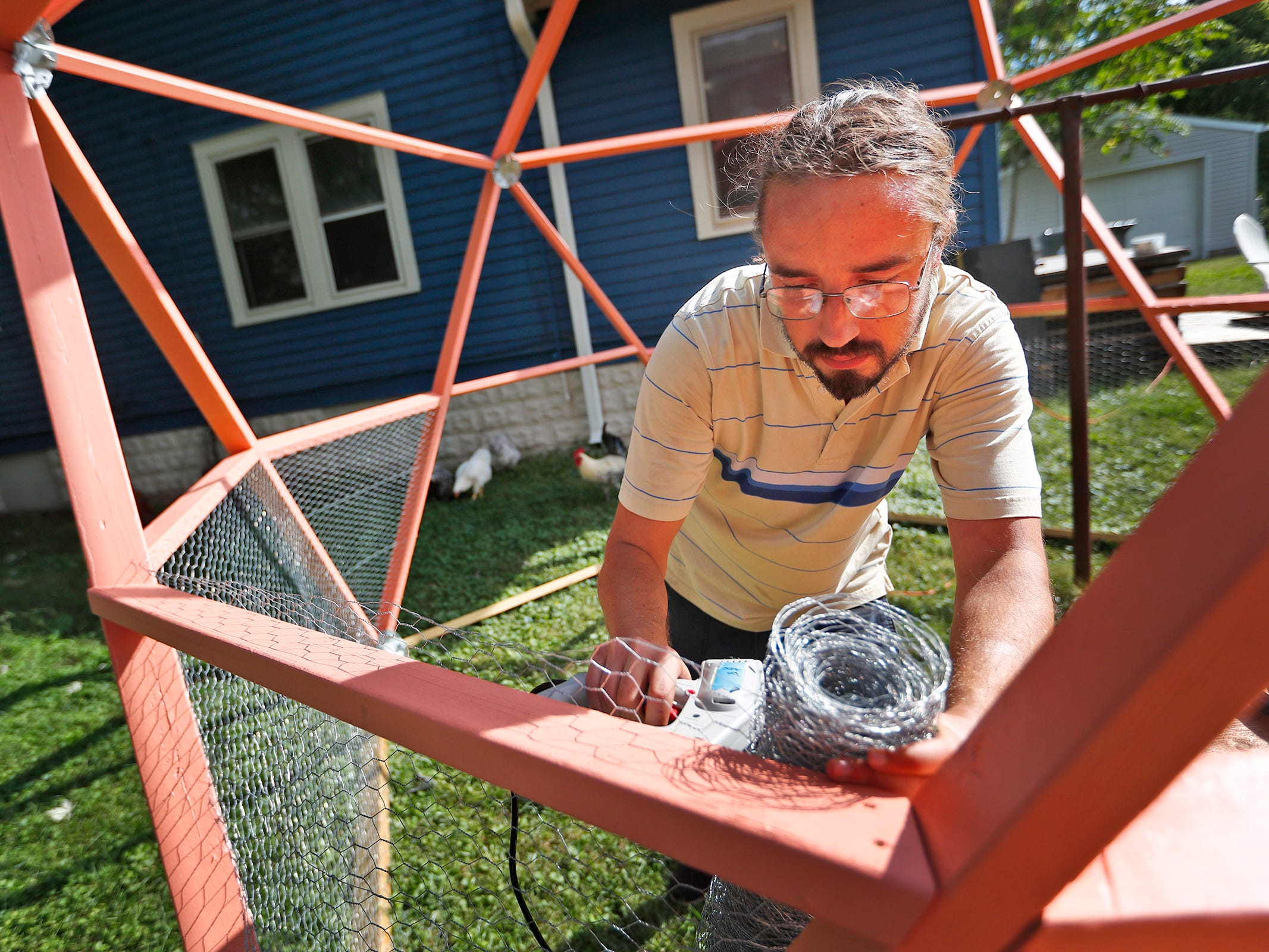 Elliot Thornton works to build a new chicken coop structure outside the Tube Factory Artspace, Tuesday, Oct. 9, 2018. In this same yard, the new Chicken Chapel of Love will be built.  The Vegas-style wedding chapel in the backyard of the Tube Factory Artspace will be complete with chickens.  You can bring your own minister or ask one of the ordained Big Car staff to officiate.  The chapel also will be a meditation center that connect the art world to the earth.  Also on the site are a bee sanctuary, raised gardens, and chicken coops.