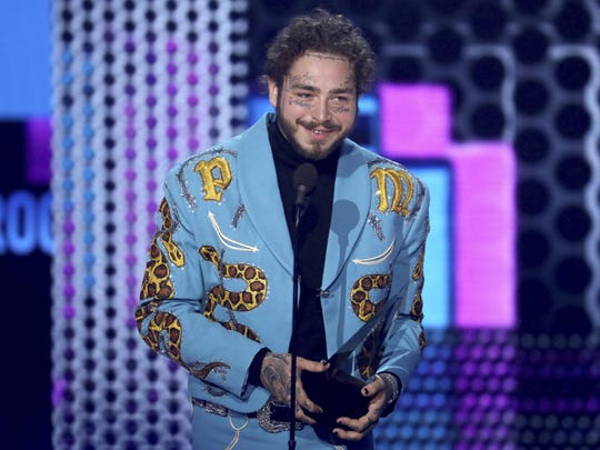 Post Malone, wearing a suit made by Indianapolis tailor Jerry Lee Atwood, accepts the favorite male pop/rock artist award at the 2018 American Music Awards ceremony.