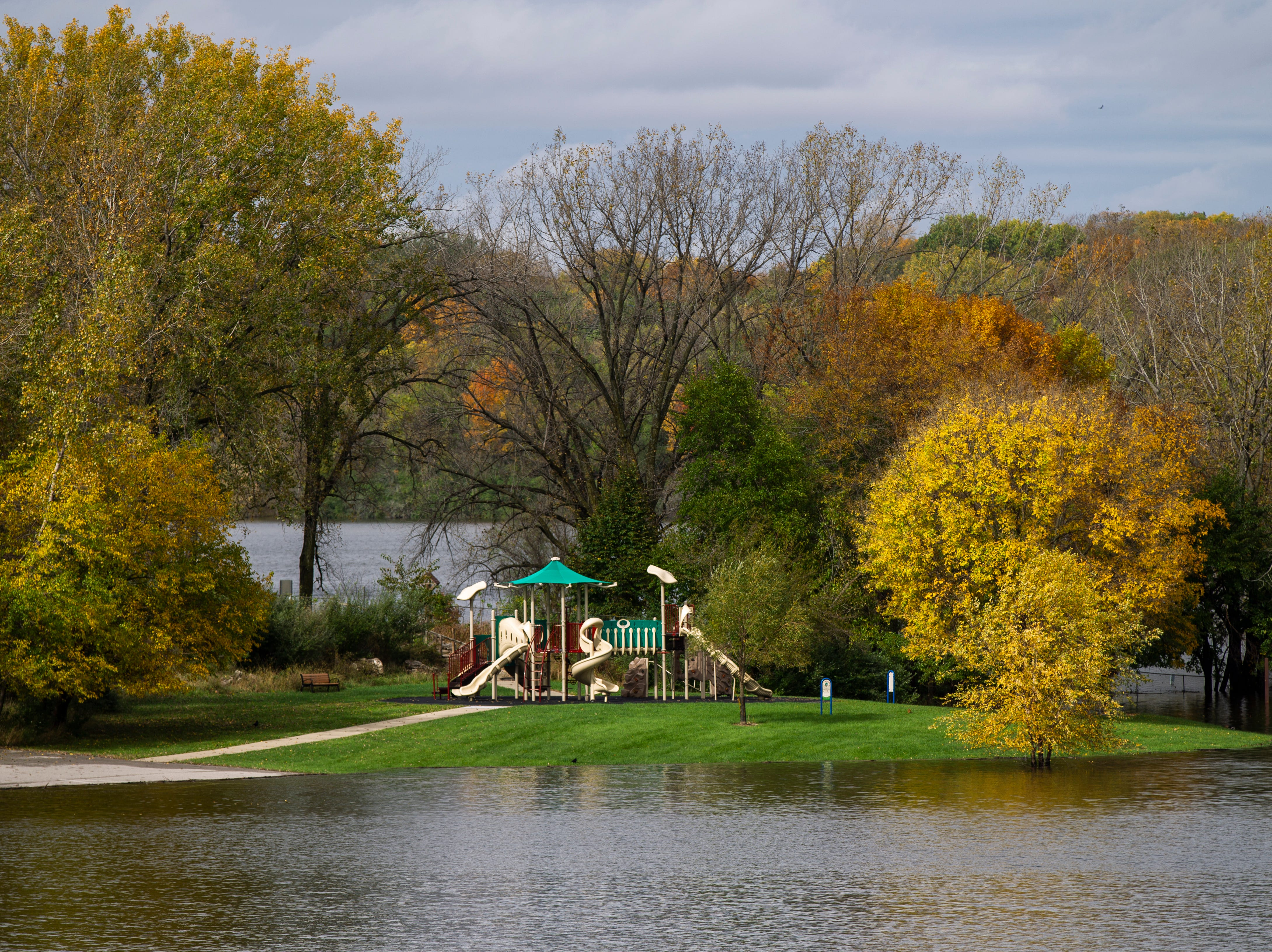 Water raises out past the beach to surround a play structure on Wednesday, Oct. 10, 2018, at the Coralville Lake dam.