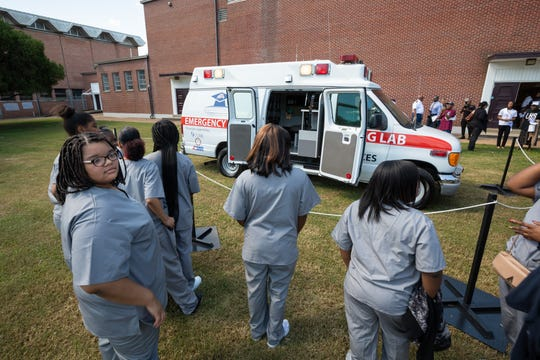 Students in Lanier High's Health Services Academy line up to get a first look at a retired ambulance donated to their program by American Medical Response.