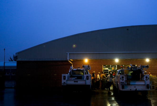 Line workers hold an early morning meeting under an overhang during a rainstorm before leaving to assist with Hurricane Michael recovery efforts in South Georgia at Southwest Tennessee Electric Brownsville Office in Brownsville, Tenn., on Wednesday, Oct. 10, 2018.