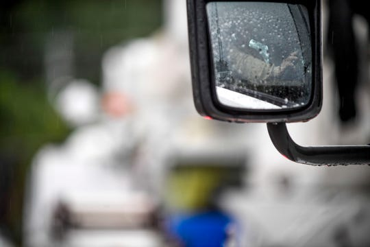A truck driver rests his hand on the wheel while waiting to leave with two other crews en route to South Georgia to assist with Hurricane Michael recovery efforts at Southwest Tennessee Electric Brownsville Office in Brownsville, Tenn., on Wednesday, Oct. 10, 2018.
