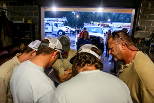 Line workers huddle together to look at a cell phone that has the route they will take mapped out on a navigation app at Southwest Tennessee Electric Brownsville Office in Brownsville, Tenn., on Wednesday, Oct. 10, 2018.