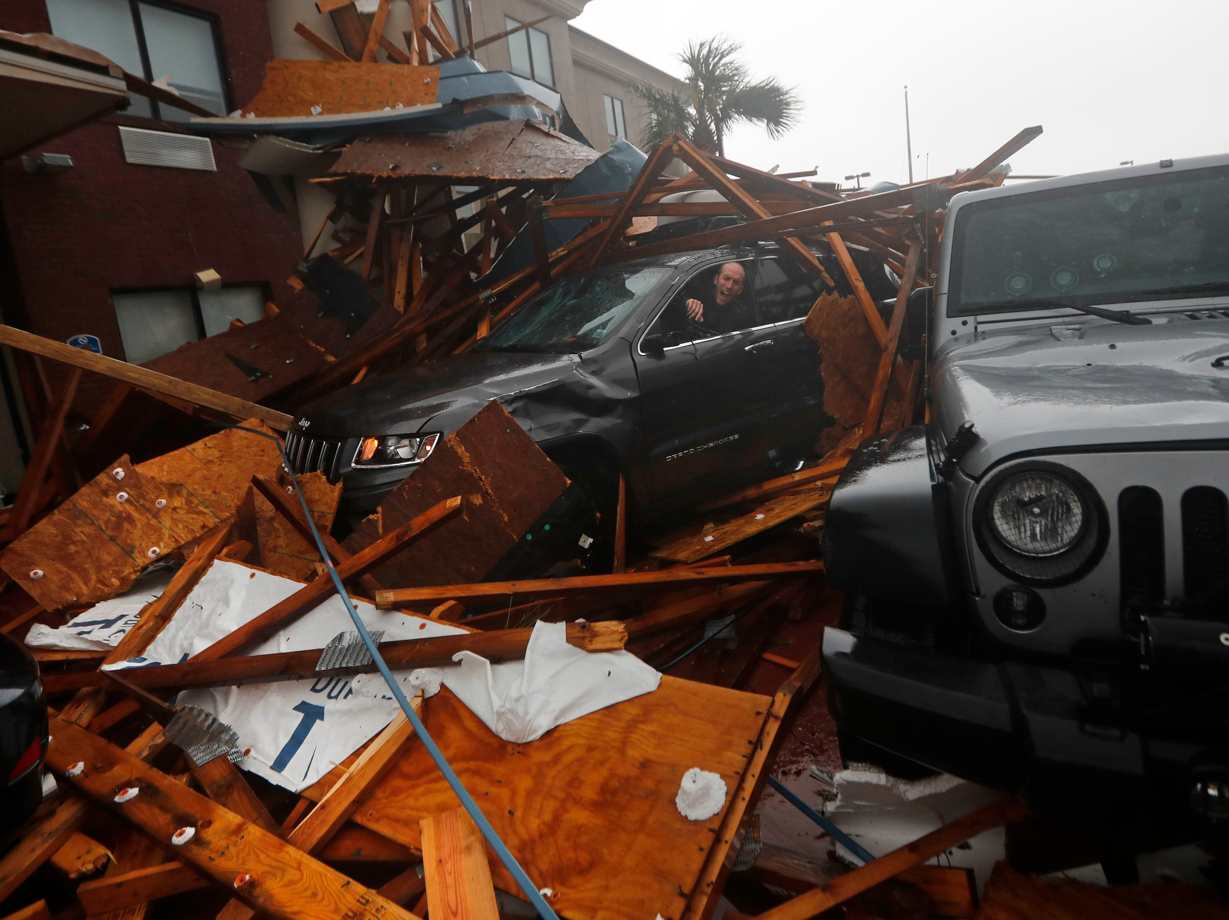 A storm chaser climbs into his vehicle during the eye of Hurricane Michael to retrieve equipment after a hotel canopy collapsed in Panama City Beach, Fla., Wednesday, Oct. 10, 2018.
