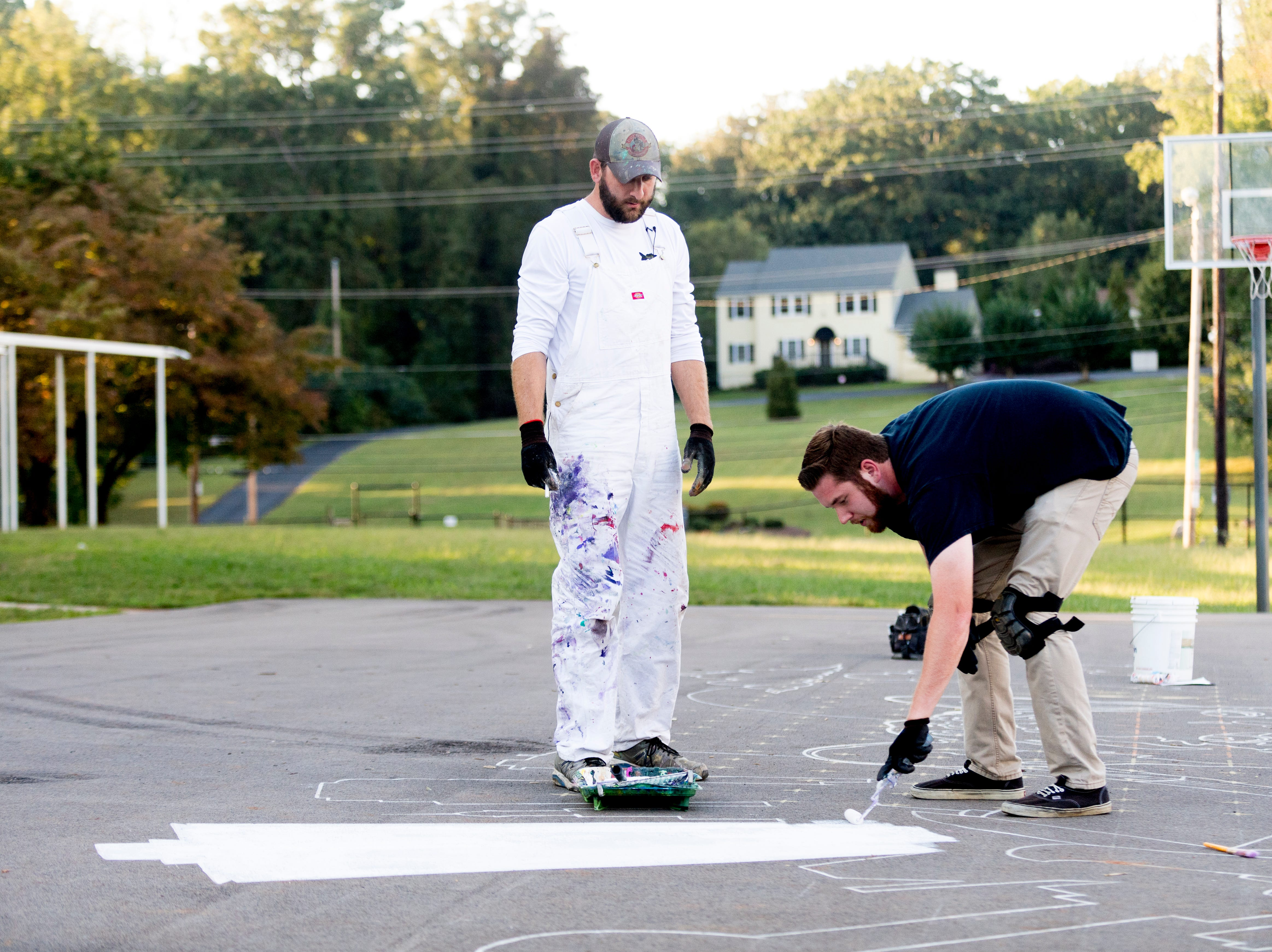 News Sentinel reporter Ryan Wilusz and local muralist Curtis Glover work on a mural at the outdoor basketball court at Pond Gap Elementary School in Knoxville, Tennessee on Thursday, October 4, 2018. Glover is quickly becoming known in the Knoxville area for his incredibly detailed murals.