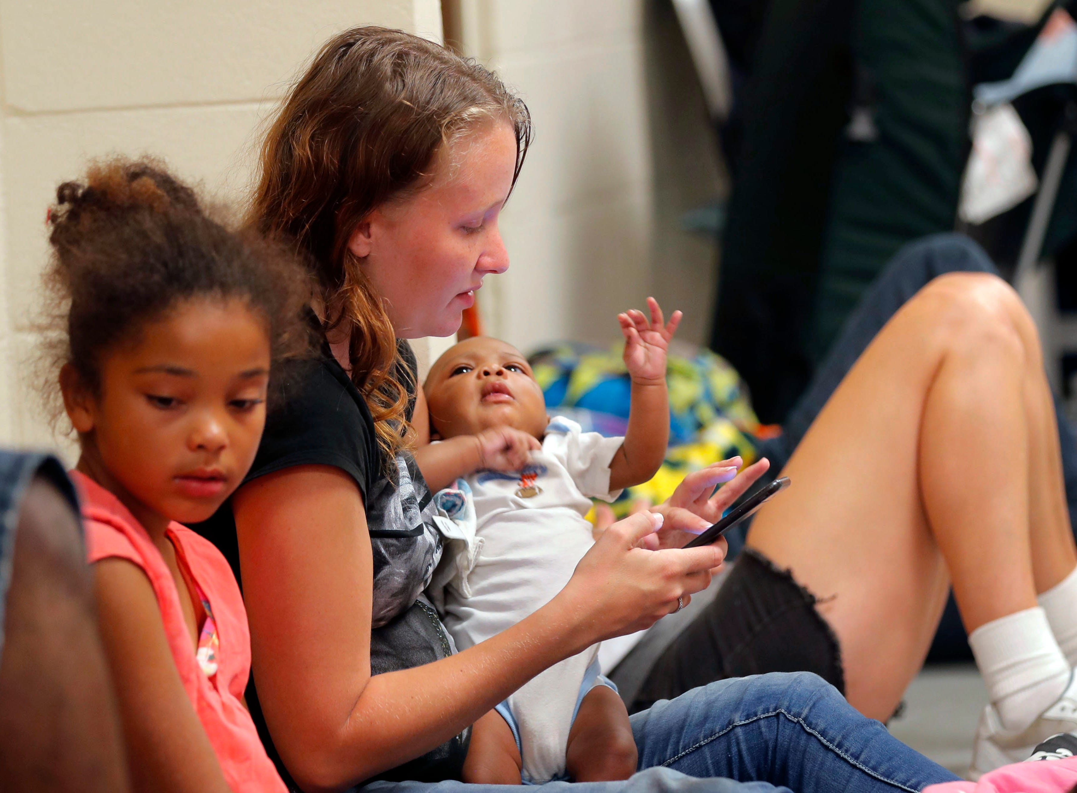 CORRECTS NAME OF HURRICANE TO MICHAEL FROM MATTHEW - Ashley Fillingim holds her godson Jerah'monie Anthony Bell, 2 months, at an evacuation shelter set up at Rutherford High School, in Panama City Beach, Fla., in advance of Hurricane Michael, which is expected to make landfall, Wednesday, Oct. 10, 2018.