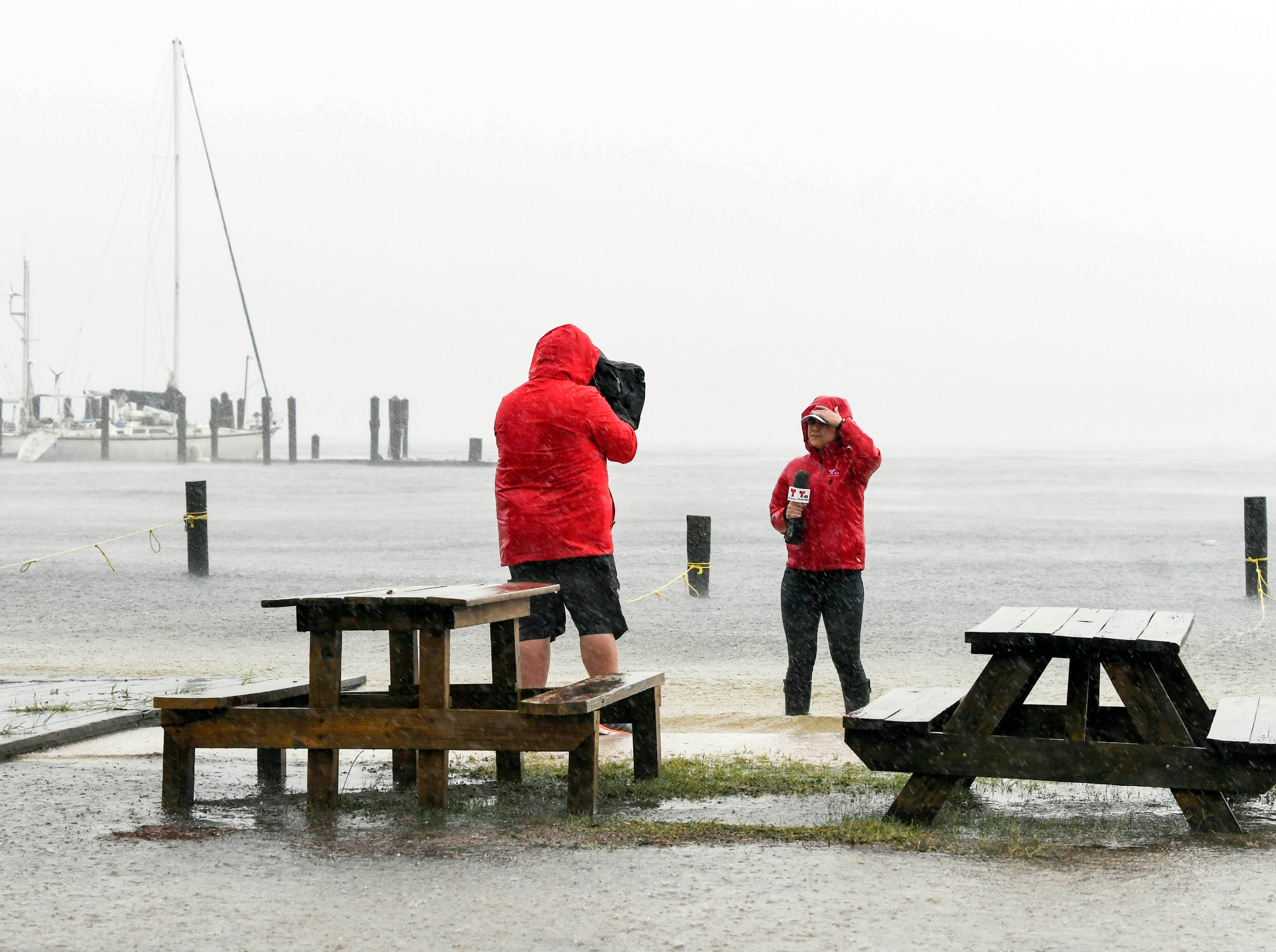 Oct 10, 2018; Panama City, FL, USA; A television crew stands in water from St. Andrews Bay pushed inland by Hurricane Michael.