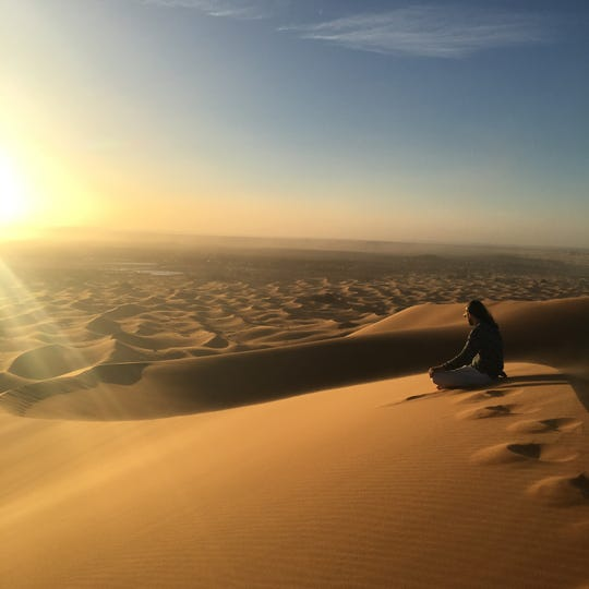 Philip Baites sits on top of a dune in the Sahara Desert.