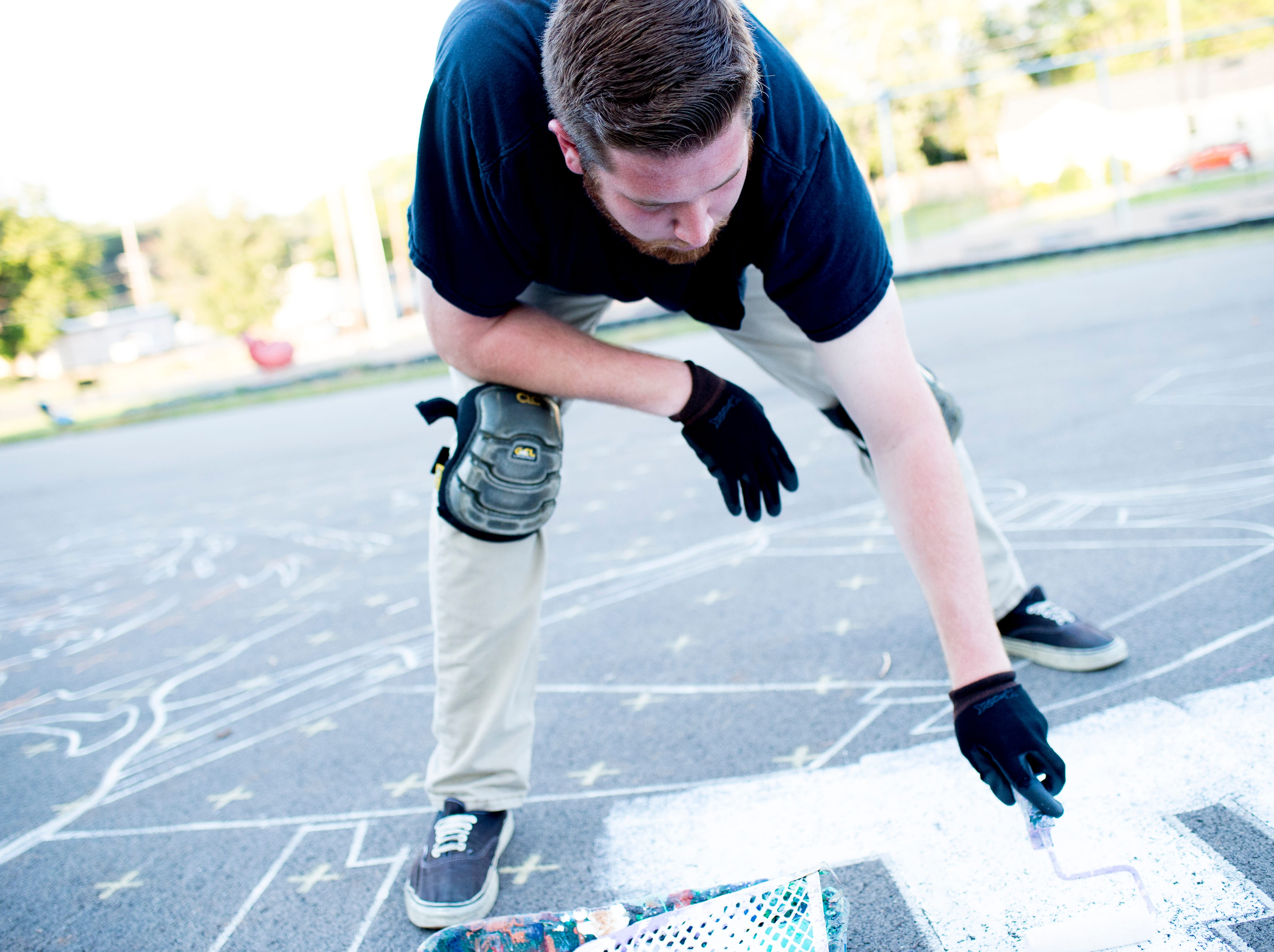 News Sentinel reporter Ryan Wilusz helps paint the outdoor basketball court at Pond Gap Elementary School with local muralist Curtis Glover in Knoxville, Tennessee on Thursday, October 4, 2018. Glover is quickly becoming known in the Knoxville area for his incredibly detailed murals.
