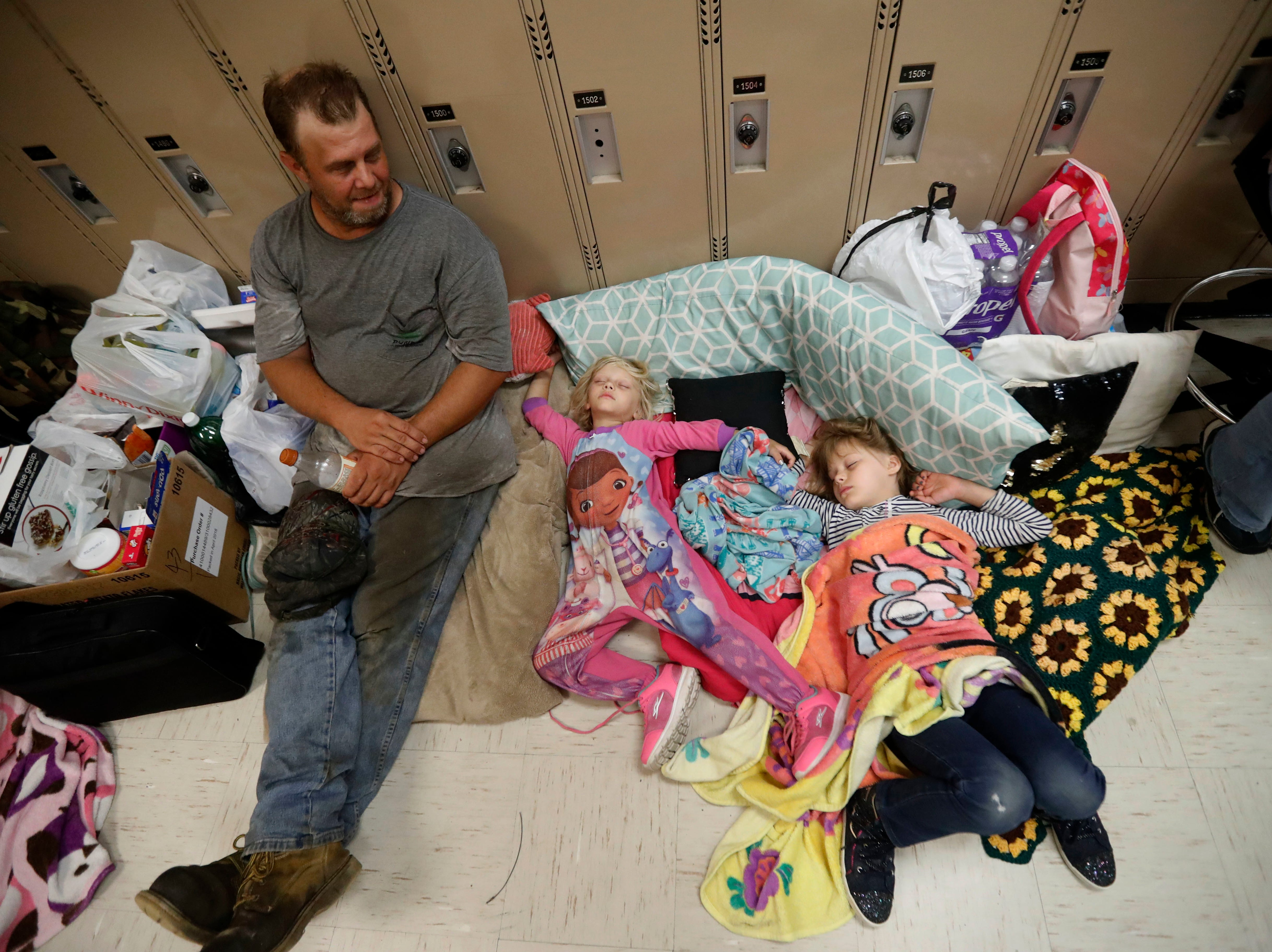 Earnest Sweet sits while his daughters Terri, 4, center, and Anna, 7, sleep at an evacuation shelter set up at Rutherford High School, in advance of Hurricane Michael, which is expected to make landfall today, in Panama City Beach, Fla., Wednesday, Oct. 10, 2018.