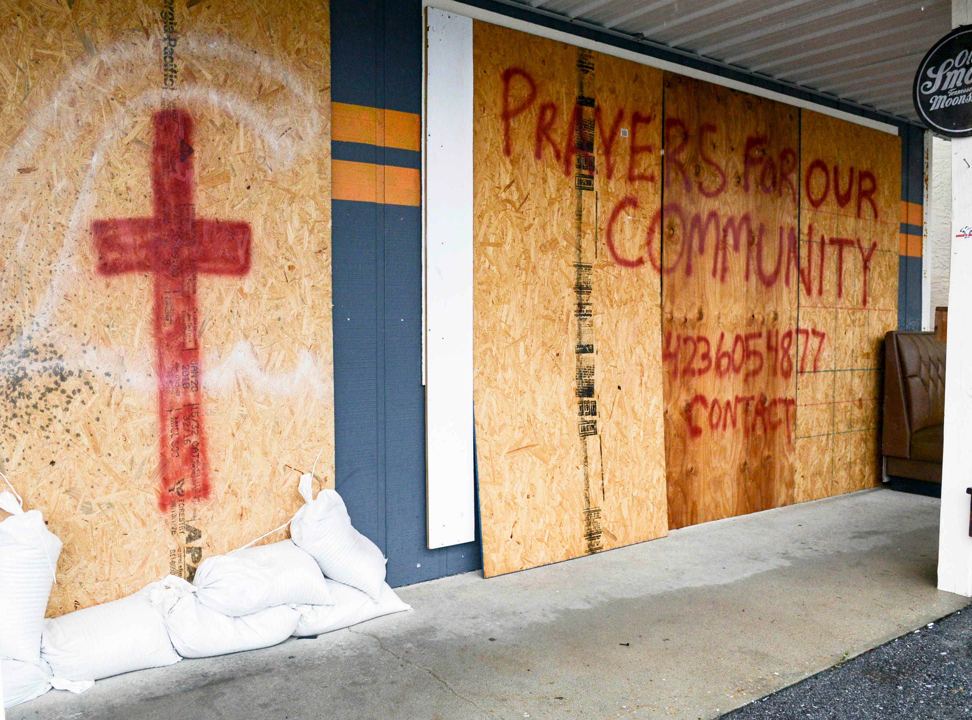 Oct 10, 2018; Panama City, FL, USA; Sandbags, boards and a prayer request guard the front of South Iron Customs motorcycle shop on Panama City Beach.