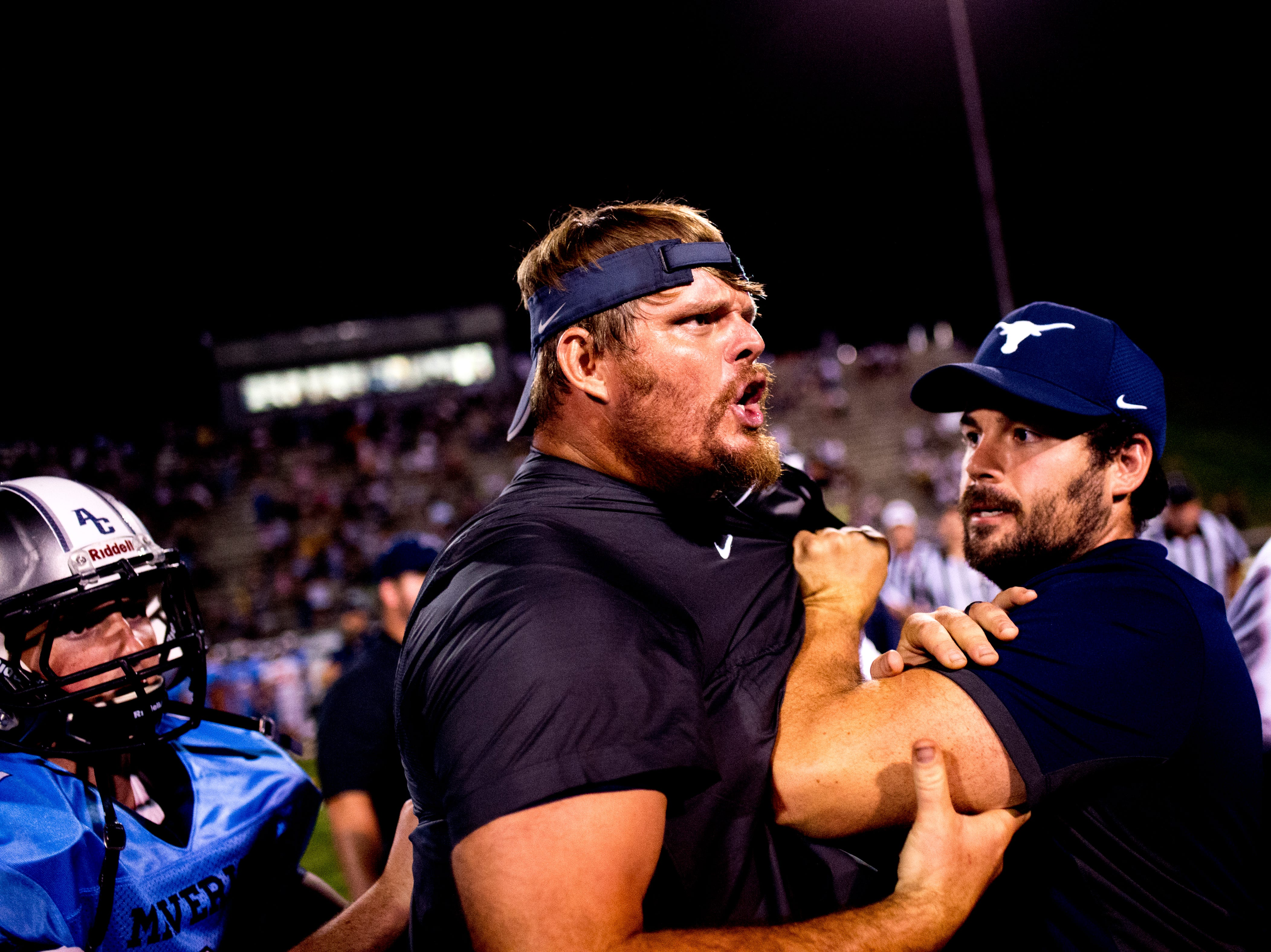 Offensive Line Coach Russ Gillum is held back by fellow team members after getting into an apparent altercation with Clinton Head Coach Randy McCamey  during a football game between Anderson County and Clinton at Anderson County High School in Clinton, Tennessee on Thursday, September 6, 2018.