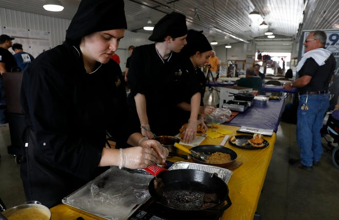 Olivia Sherfey, a senior in the Lancaster High School culinary arts program, checks the temperature of a hamburger slider before taking it out of a pan Wednesday afternoon, Oct. 10, 2018, at he Fairfield County Fair in Lancaster. The culinary arts program took over the local food booth at the Ed Sands building to display some of the students' award winning recipes.