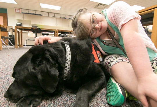 Brighton High School student JoLee White and therapy dog Caesar bond in White's classroom Wednesday, Oct. 10, 2018.
