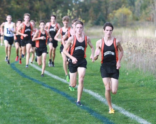 Brighton's Zachary Stewart (first) and Jack Spamer (second) lead the pack early in the race against Hartland and Howell on Tuesday, Oct. 9, 2018.