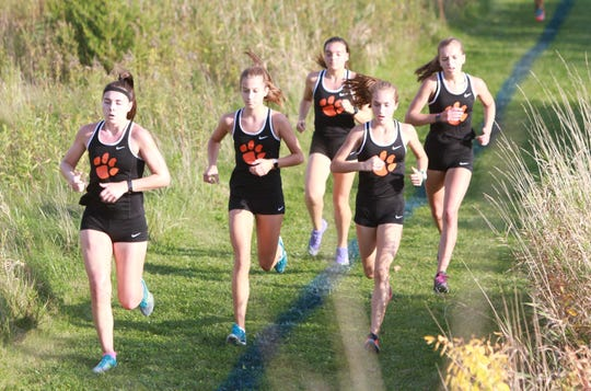 Maddie Brown (left) leads a pack of five Brighton runners at the front near the halfway mark of a double-dual meet against Hartland and Howell on Tuesday, Oct. 9, 2018.