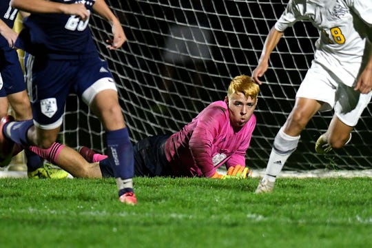 East Lansing's goalkeeper Nekko Criswell-Grinage, center, focuses on the ball after saving a goal during the second half on Tuesday, Oct. 9, 2018, at Okemos High School.