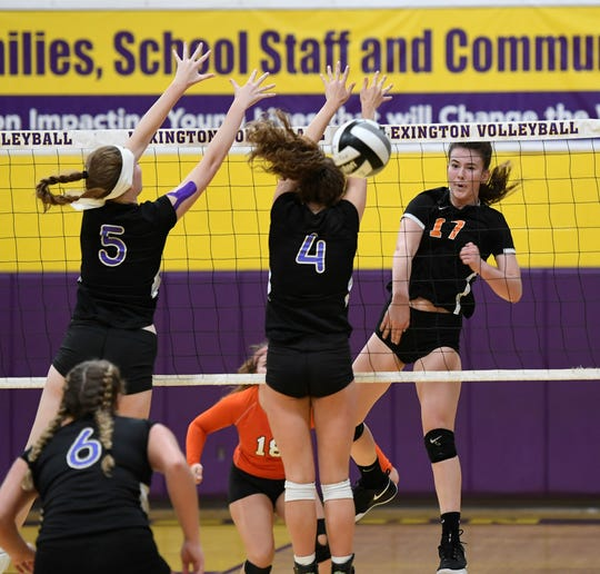 Ashland's Karli Shepherd hits the ball past Lexington's Audra Kocher (4) and Natalie Beer (5) during an OCC match at Lexington High School on Tuesday.
