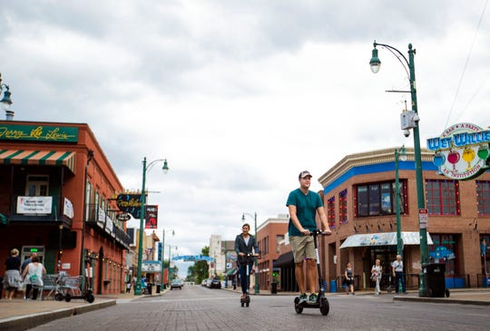 Riders make their way across a street on Beale Street on Bird electric scooters on Oct. 10, 2018.