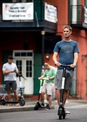 A rider makes his way down Beale Street on a Bird electric scooter on Oct. 10.