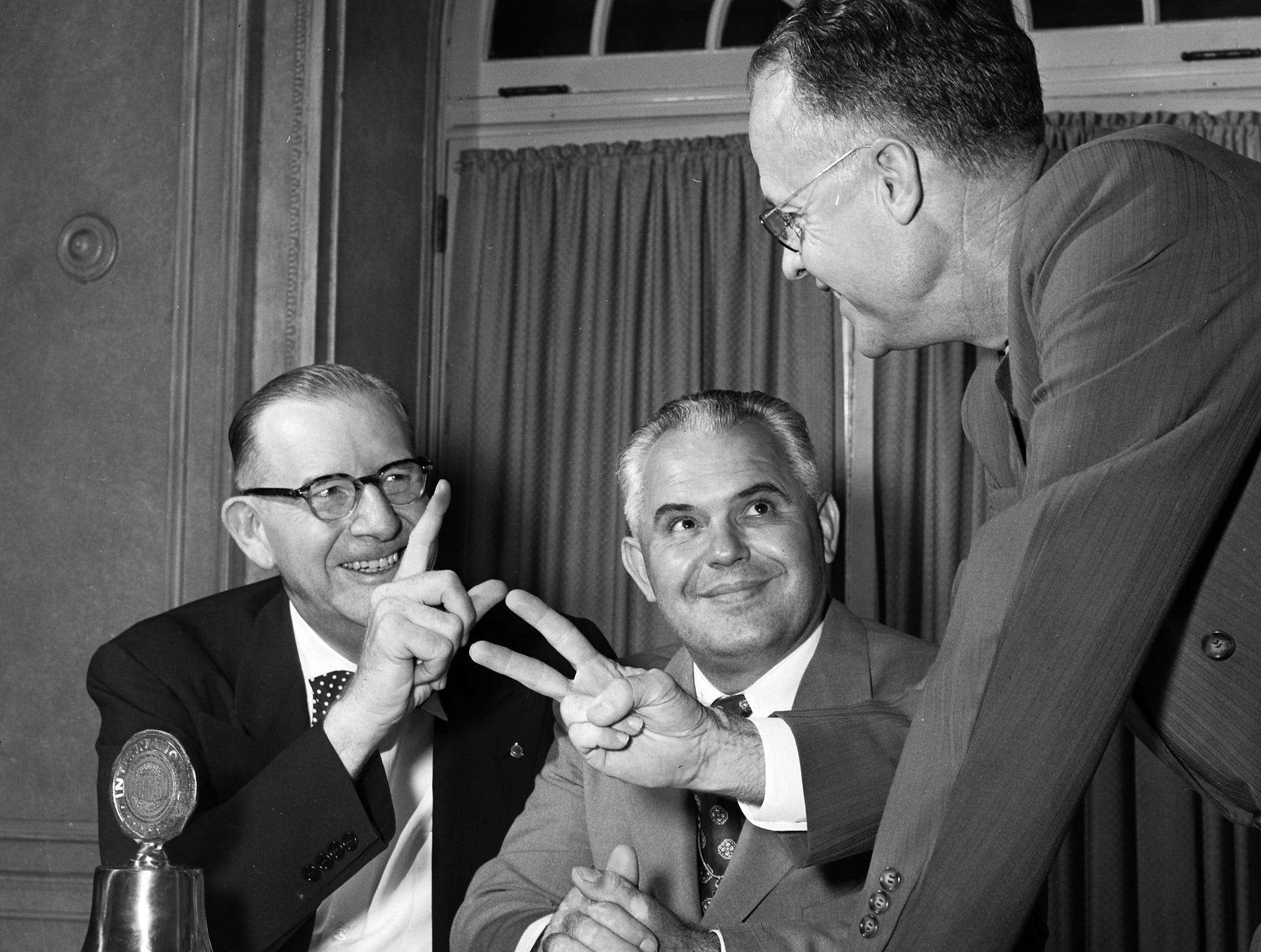 "Grady T. Kay of Birmingham (Left), international president of Civitan, holds up one finger in October 1951 indicating his own Birmingham club was the first one established in the world, ""but second"", says Lomax Springfield (Right), president of the Memphis club, ""was the club in Memphis.""  The man between is John Bond of Clarksville, district governor of Civitan for West Tennessee."