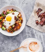 Roasted Sweet Potatoes & Brussels Sprouts with Eggs and Maple Pecans is served with a maple Sriracha yogurt.