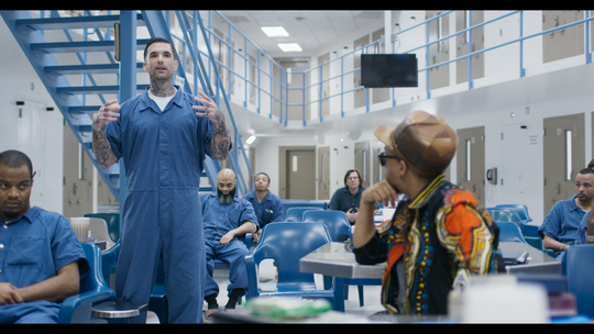 "Garland Carr, an inmate at Richmond City Jail, speaks as rapper and producer Todd ""Speech"" Thomas looks on in a scene from ""16 Bars."" The documentary follows four prisoners participating in a music rehabilitation program."