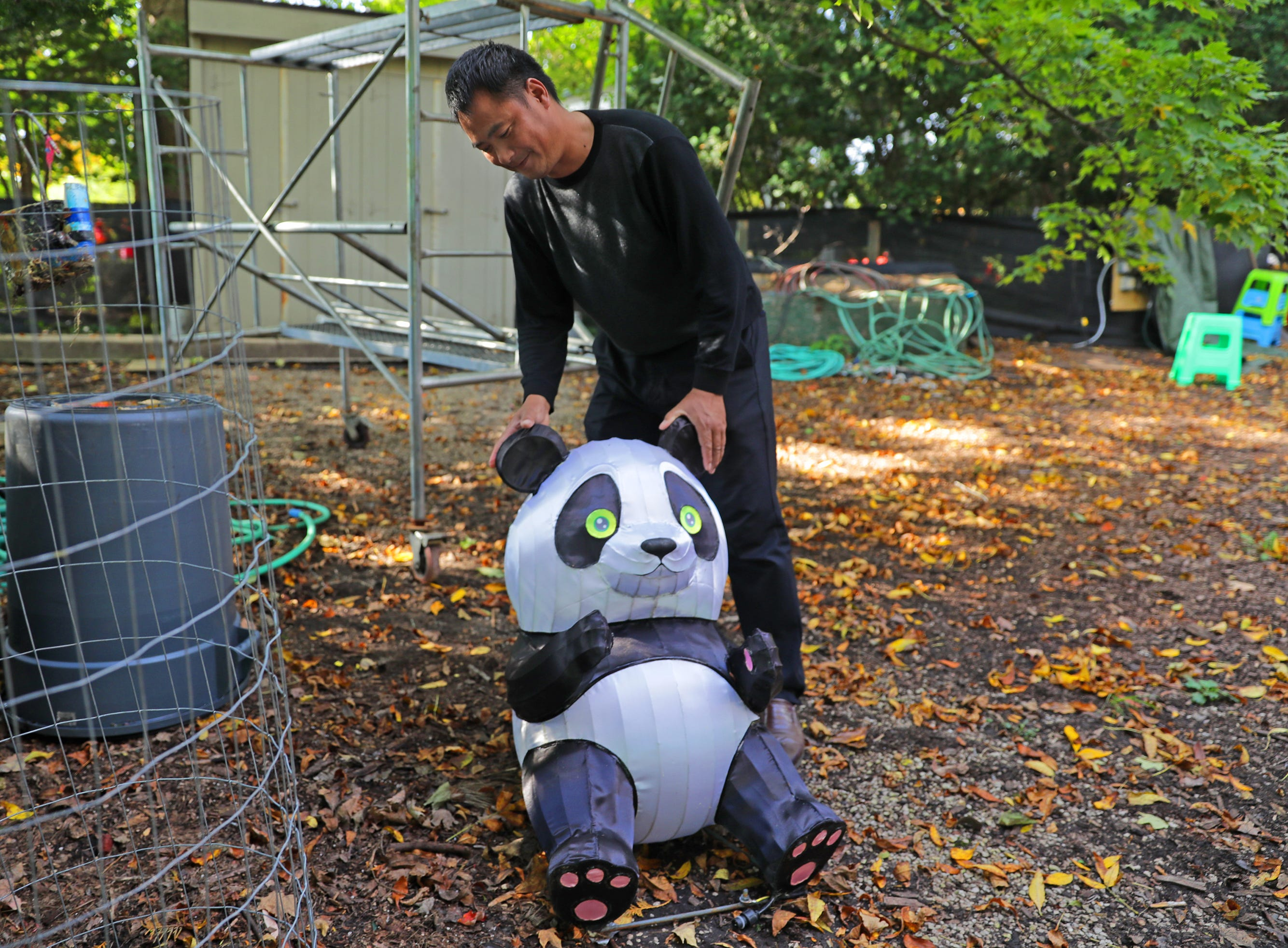 Liu Yufu, the China Lights supervisor of workers, looks over a panda display piece in need of repair.