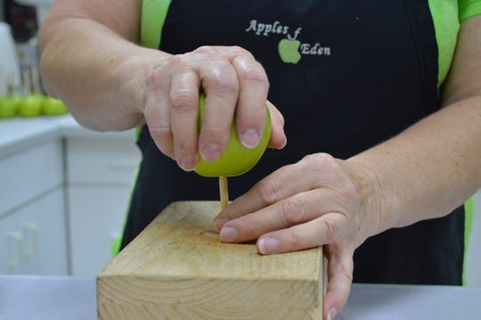 At Apples of Eden, a block holds the stick in place and the apple is pushed down onto it.