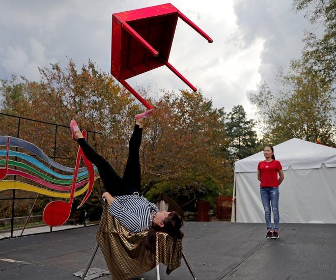 Zhao Xiaoli, a foot juggler at China Lights: Panda-Mania lantern festival at Boerner Botanical Gardens, practices juggling a table while Chow Jie, a Chinese yo-yo performer, looks on.