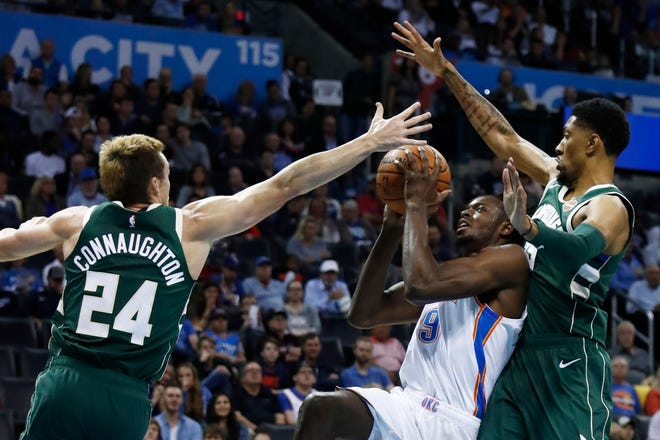 Bucks players Pat Connaughton  and Christian Wood try to block the shot of Oklahoma City's Jerami Grant.