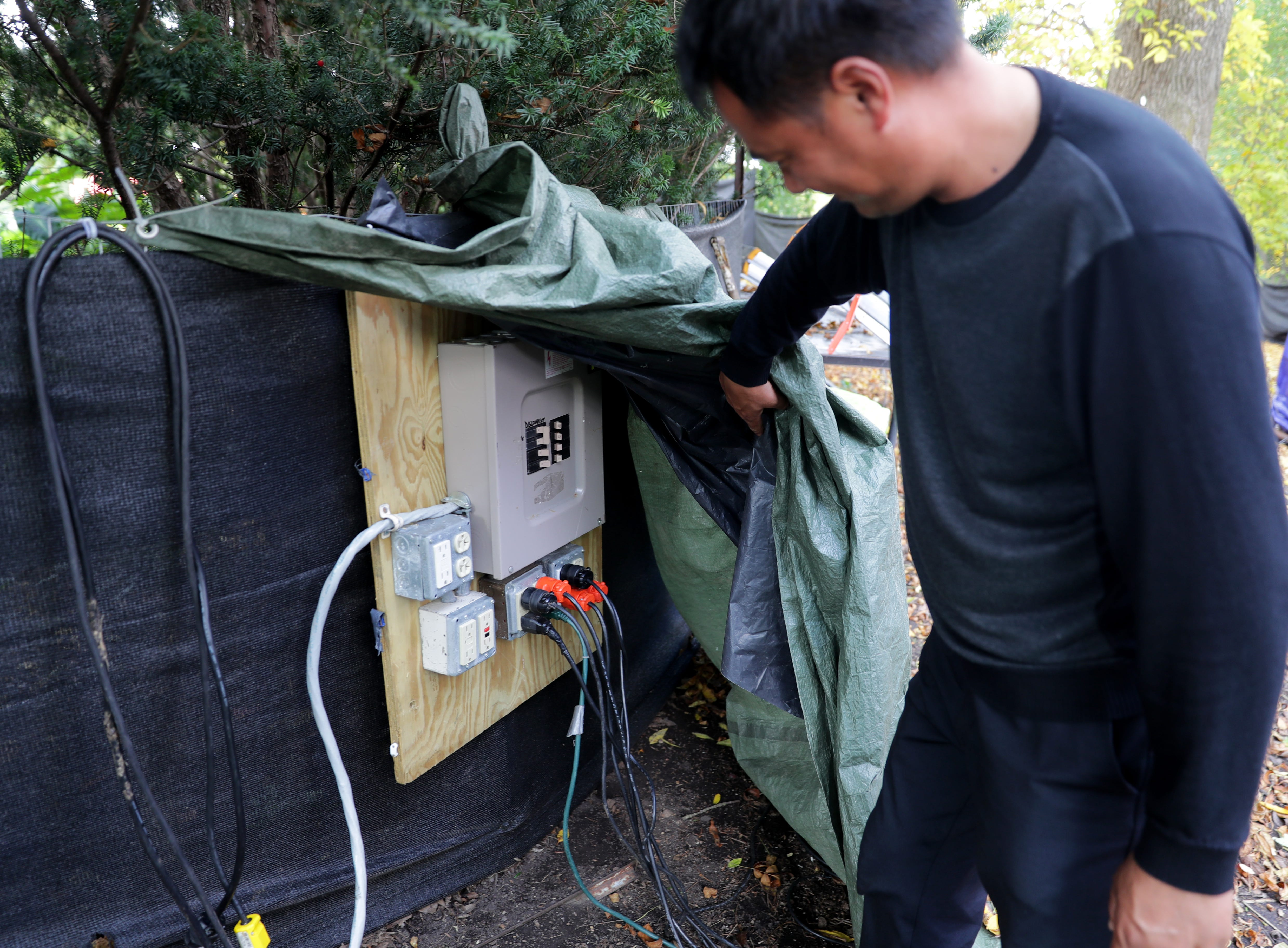 Liu Yufu, the China Lights supervisor of workers, looks over an electrical box used to power supplies.
