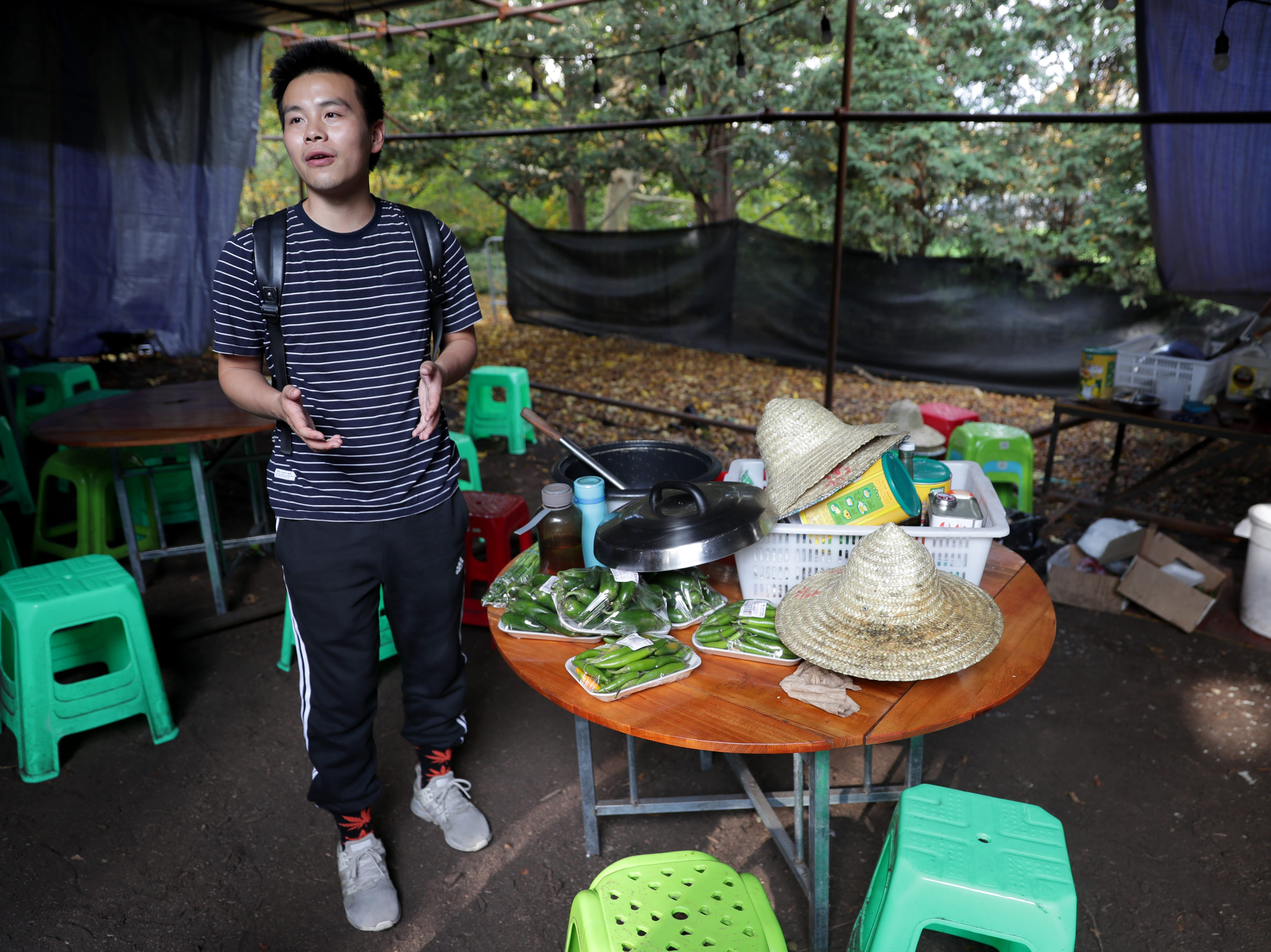 Craig Chen, the China Lights site supervisor, talks in the cook tent where workers eat meals.
