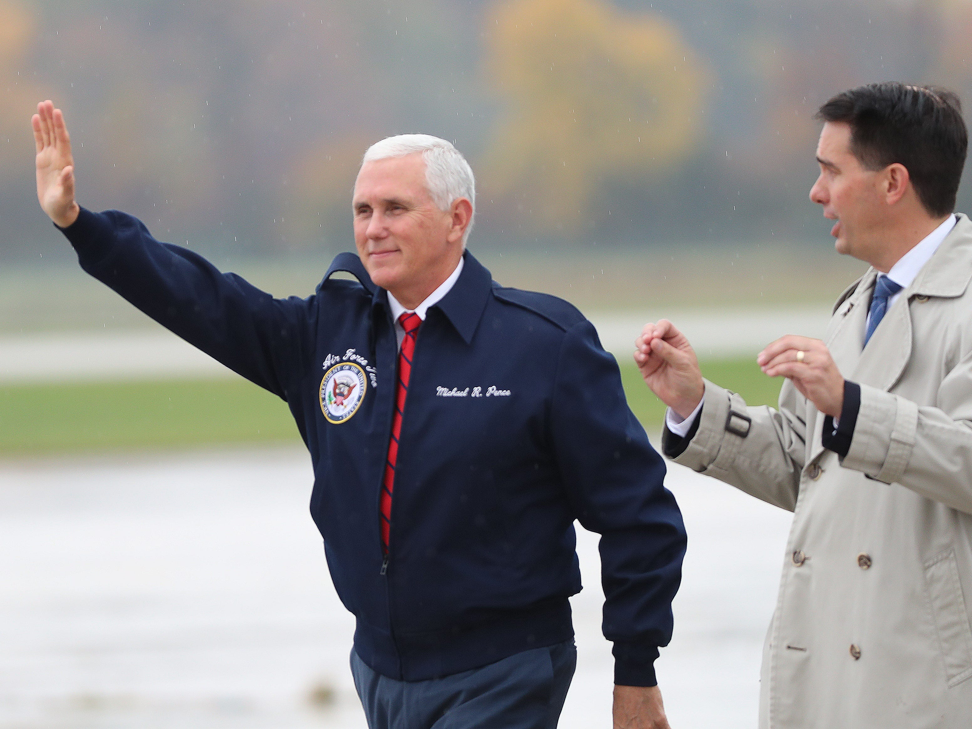 Vice President Mike Pence waves after arriving in Green Bay Wednesday, Oct. 10, 2018, in Ashwaubenon. Gov. Scott Walker is at right.