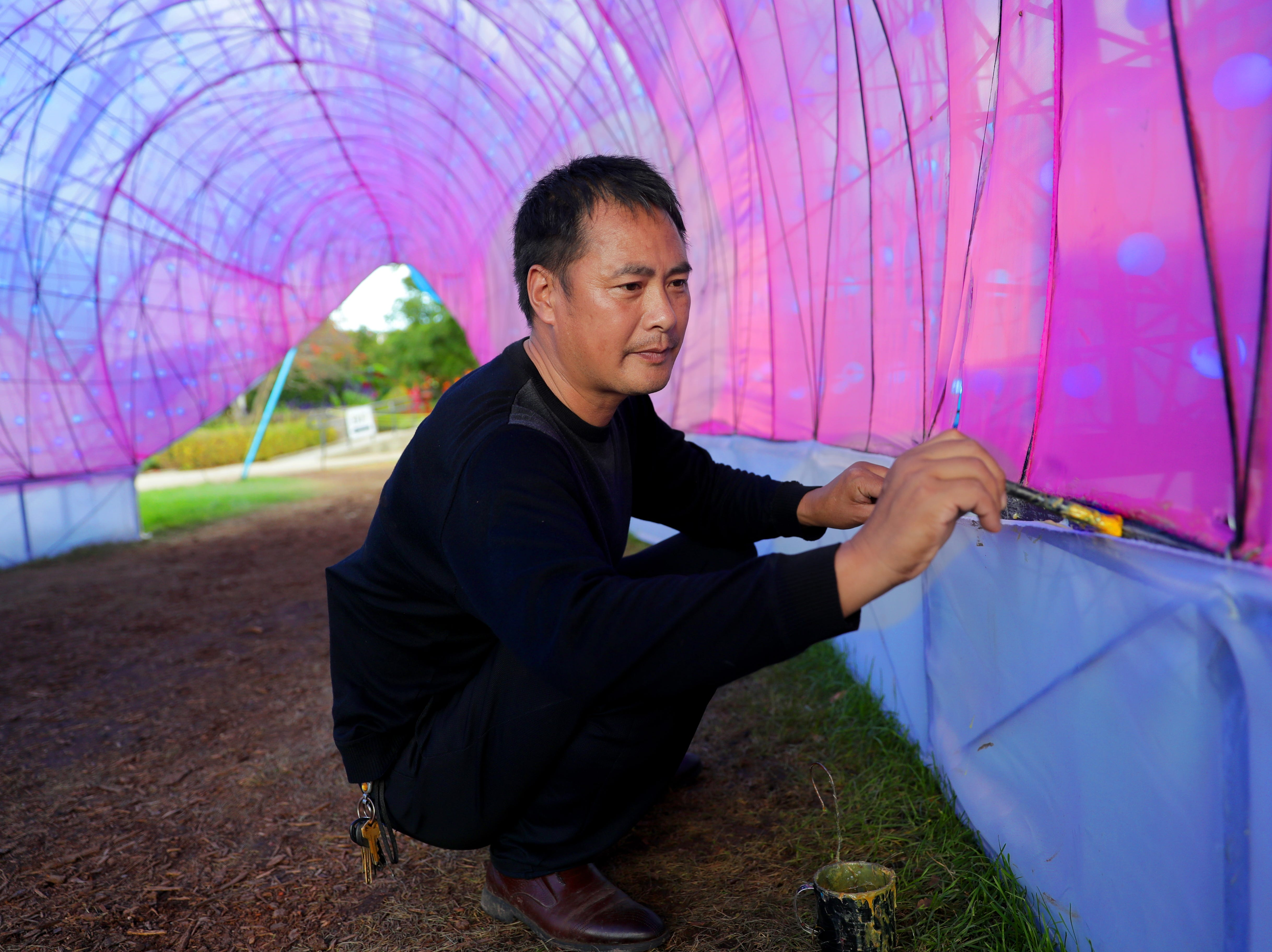 Liu Yufu, the China Lights supervisor of workers, uses an adhesive to secure fabric inside a 65-foot-long shark sculpture. Behind making the China Lights festival at Boerner Botanical Gardens at Whitnall Park run smoothly are the Chinese artisans and entertainers.