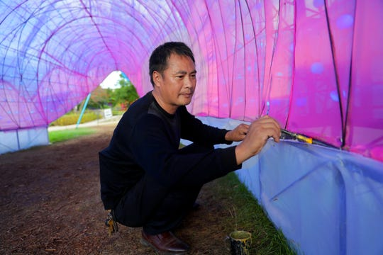 Liu Yufu repairs torn fabric inside the 65-foot-long shark lantern sculpture at China Lights: Panda-Mania lantern festival at Boerner Botanical Gardens. He is supervisor of artisans responsible for maintaining lighted, fabric lantern sculptures during the festival.