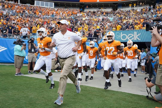 Tennessee coach Jeremy Pruitt leads his team onto the field against West Virginia Bank of America Stadium on Sept. 1, 2018, in Charlotte, NC.