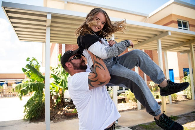 J. D. Parker School of Science, Math and Technology third-grader Alincia Karr, 9, is hoisted by her father, Albert Karr, both of Stuart, as they spend time together during recess for the school's Dudes Day event