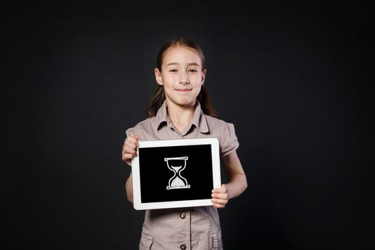 Happy Girl Shows Screen Of Tablet With Sand Clock Icon