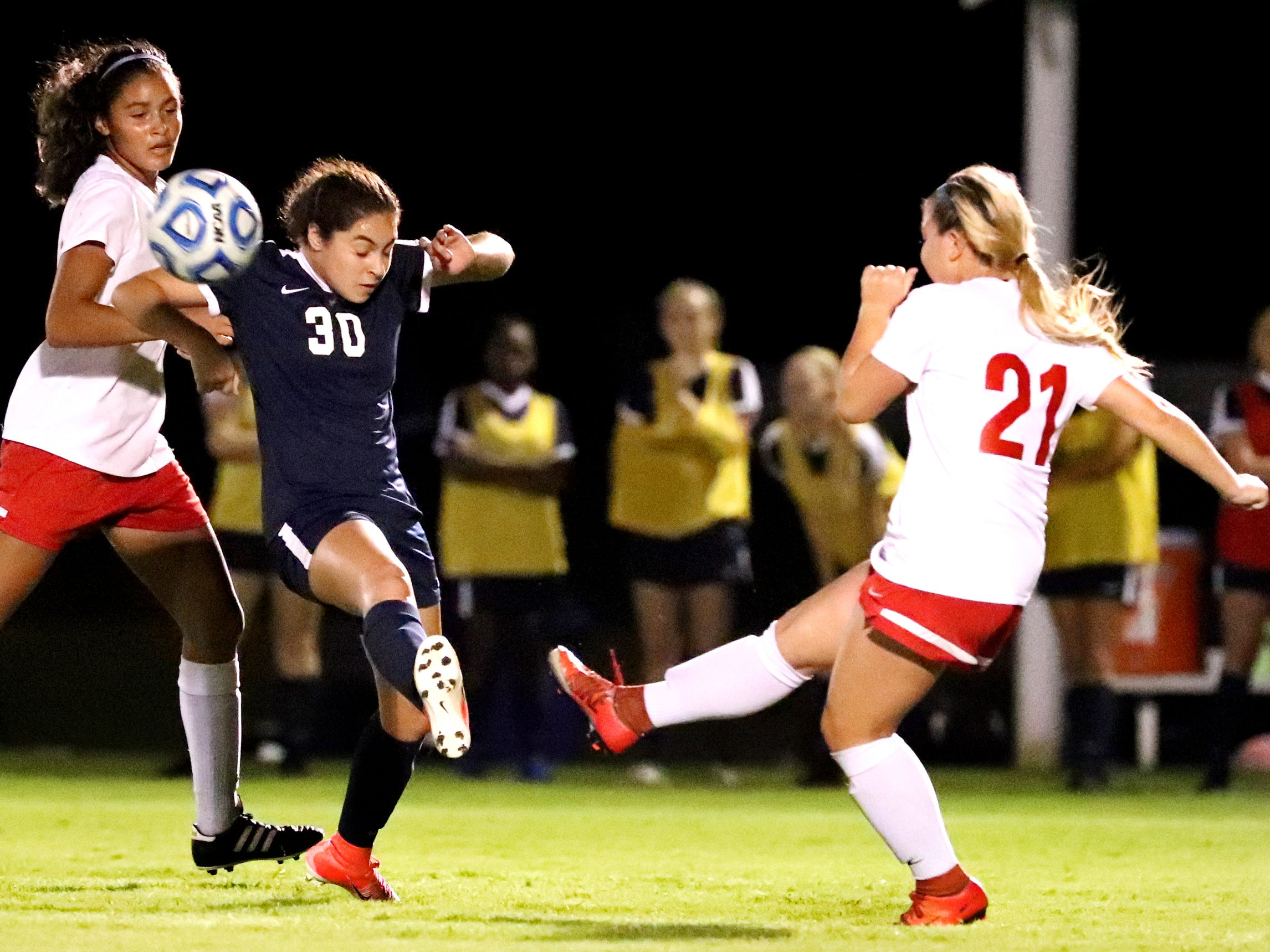 Oakland's Alysa Butera (15) kicks the ball as Siegel's Emily Sanchez (30) stops the ball and Oakland's Ella Riley(15) comes up from behind Sanchez, during the semifinals of the 7-AAA Soccer Tournament, on Tuesday,  Oct. 09, 2018 at the Siegel Soccer Complex.