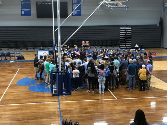 Fans from both Providence Christian and Goodpasture converge after Monday night's region volleyball match to pray for PCA freshman Marley McCauley, whose mother died that night.