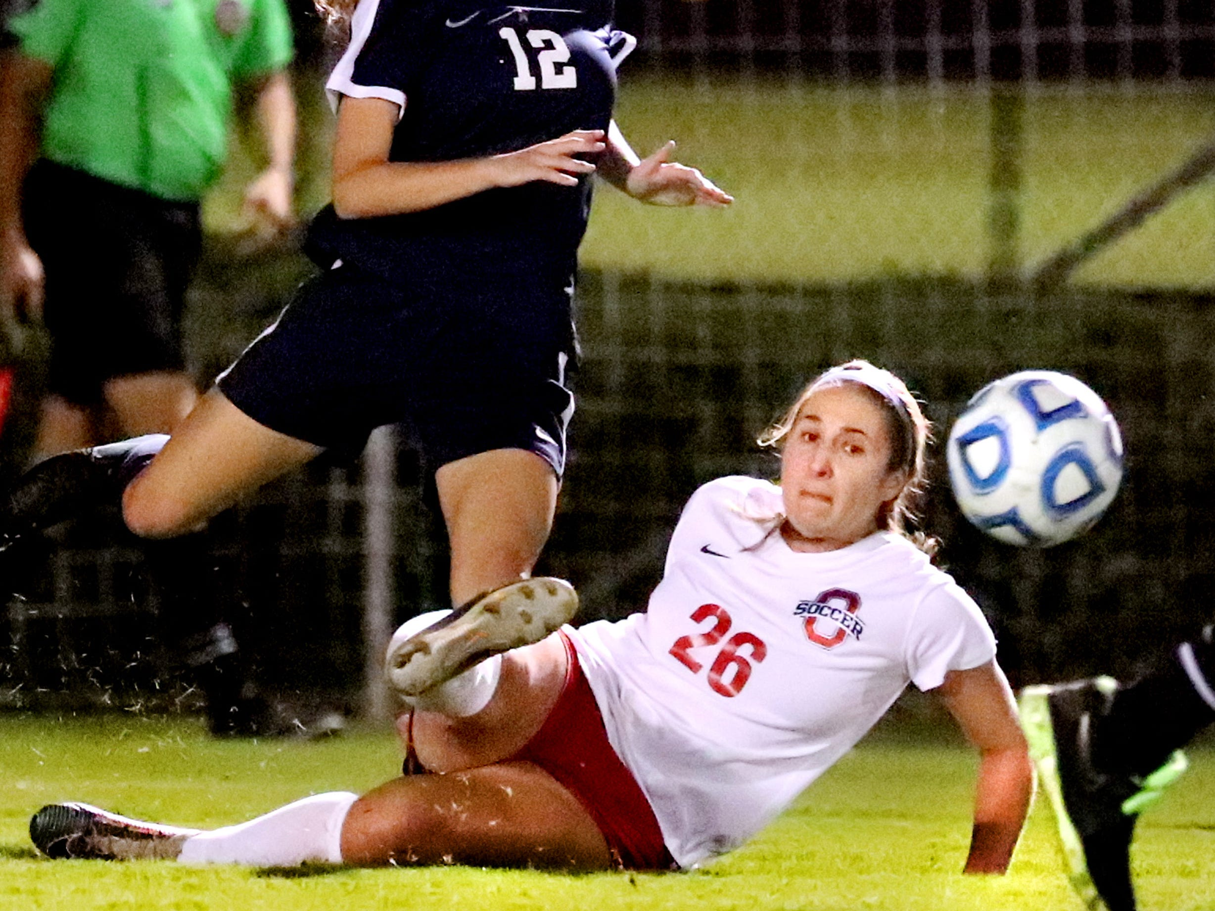 Oakland's Monica Mullaney (26) falls to the ground as she kicks the ball as Siegel's Mia Roberts (12) comes up from behind her during the semifinals of the 7-AAA Soccer Tournament, on Tuesday,  Oct. 09, 2018 at the Siegel Soccer Complex.
