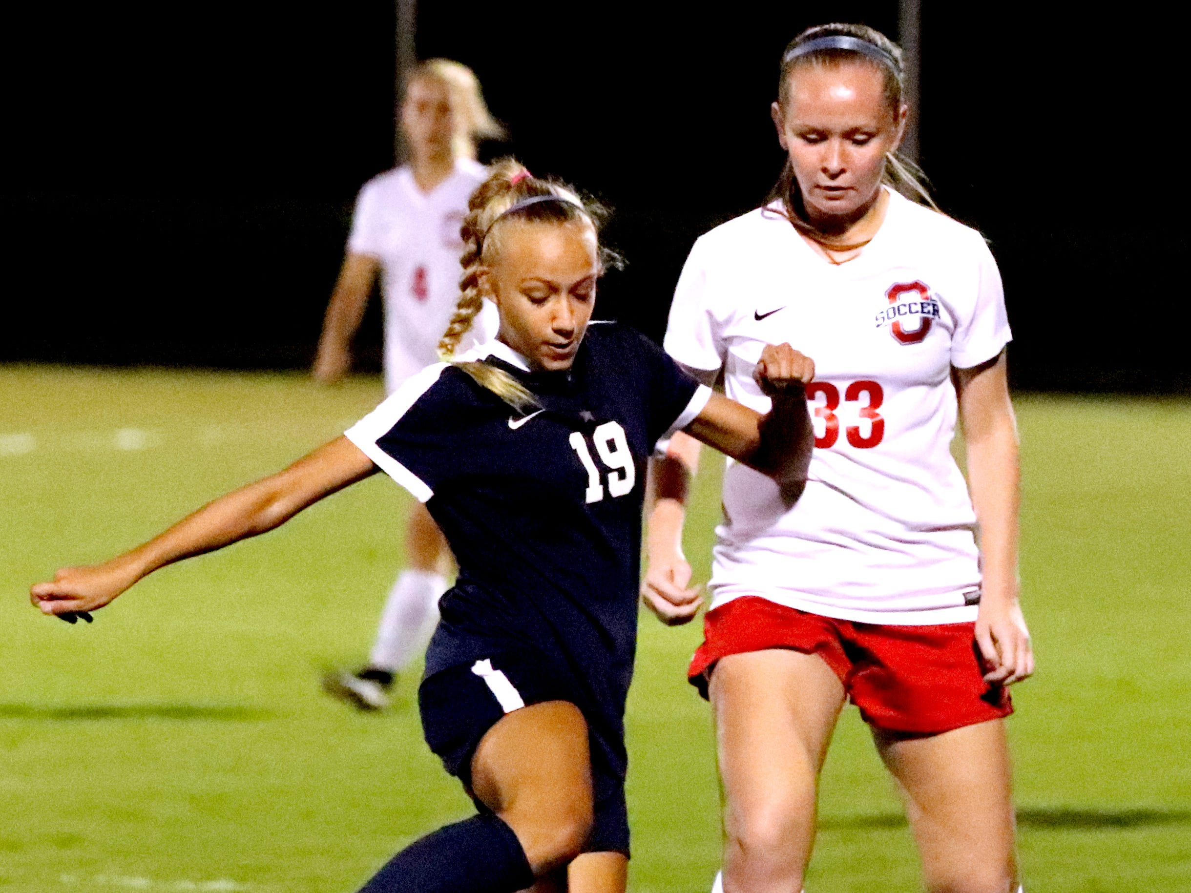Siegel's Kyla Hawkins (19) moves the ball down the field as Oakland's Reagan Parker (33) defends her in the semifinals of the 7-AAA Soccer Tournament, on Tuesday,  Oct. 09, 2018 at the Siegel Soccer Complex.